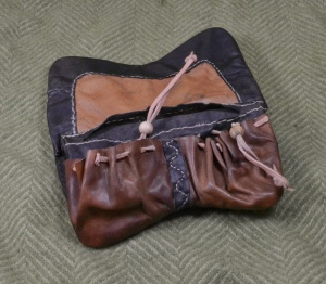 Inside of purse showing four pockets and multiple leather sections